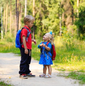 happy little boy and girl with backpacks in summer, kids go to school